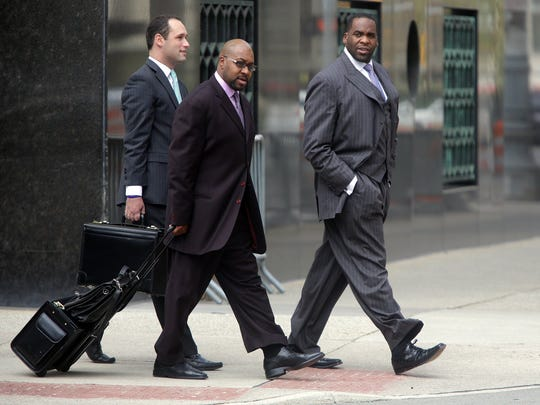 Right, former Detroit Mayor Kwame Kilpatrick and his co-defendant Bobby Ferguson, center, leave the Theodore Levin United States Courthouse in Detroit in 2012. Technical assistant for Bobby Ferguson's defense Rob Higbee is on the left.