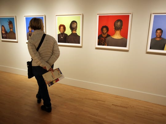 """Martha Guenther of Grand Rapids looks closer at Sonya Clark's """"The Hair Craft Project."""""""