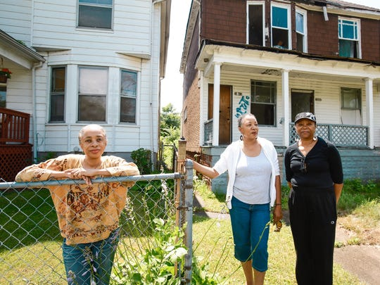 Janice Hurt-Clarke, no age given, Hattie Sanders, 60 and Vera Hurt, 68, all of Detroit, stand in front of the vacant building that sits next to their childhood home of 50+ years on Detroit's east side on Monday, July 7, 2014. After a year of bankruptcy in Detroit, their family is still hoping the city will fulfill their promise to tear down the vacant lot next to their home. While some money has been allotted for neighborhood clean up and blight removal, some residents are still waiting for the resources to trickle down.