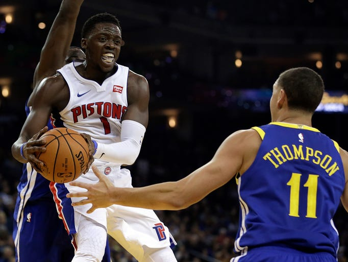 Detroit Pistons' Reggie Jackson, left, looks to pass
