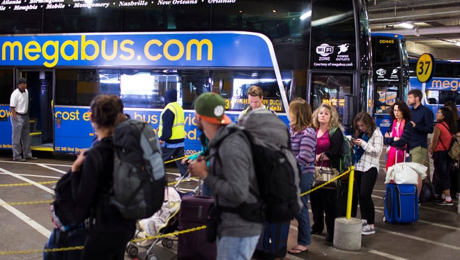 Passengers at Union Station await a bus bound for New York on Wednesday, May 13, 2015, in Washington.  Thousands of commuters and travelers had to scramble Wednesday after a deadly Amtrak train derailment shut down a critical section of the busiest railroad in North America. (AP Photo/Brett Carlsen)