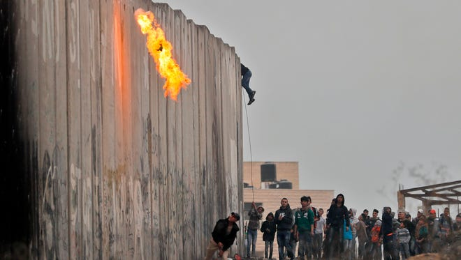 Palestinians throw a molotov cocktail and stones towards Israeli forces on the other side of a barrier at the Qalandia checkpoint in the occupied West Bank on Dec. 20, 2017, as protests continue following the President Trump's controversial recognition of Jerusalem as Israel's capital.