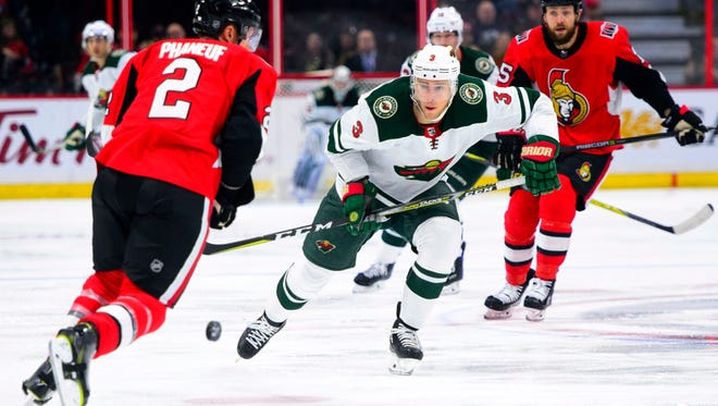 Minnesota Wild's Charlie Coyle attempts to move the puck past Ottawa Senators' Dion Phaneuf during first period NHL hockey action in Ottawa on Tuesday, Dec. 19, 2017. (Sean Kilpatrick/The Canadian Press via AP)