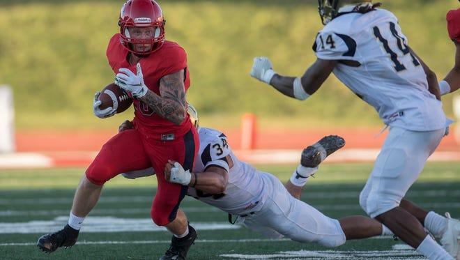 Dixie State University wide receiver Connor Miller (26) avoids a Fort Lewis College tackle during the game at DSU Saturday, September 8, 2018.
