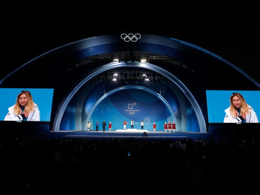 FILE - In this Feb. 13, 2018, file photo, women's halfpipe medalists from left center, China's Liu Jiayu silver, United States' ChloeKim, gold, also seen on screens, and United States' ArielleGold, bronze, attend their medals ceremony at the 2018 Winter Olympics in Pyeongchang, South Korea. Three weeks after winning at the Olympics and transforming herself from a mere snowboarder into a full-fledged celebrity, 17-year-old Chloe Kim is the first to admit she never realized what a big deal her victory would be. (AP Photo/Morry Gash, File)