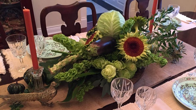 Clinton Whitney Downing created this Thanksgiving centerpiece for Sue Nawas. He combined fresh produce with botanicals for the main grouping, flanked by Nawas' Waterford candlesticks and antiqued pheasants.