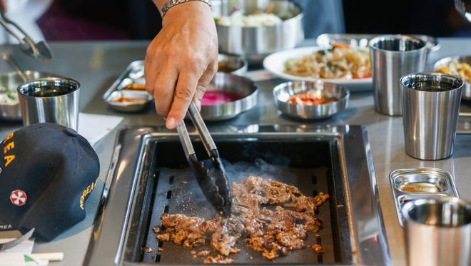 Brian Yang, center, grills a batch of beef bulgogi at Bawi during a special event for Korean War veterans at the new all-you-can-eat Korean barbecue restaurant located at 4121 S. National Ave.