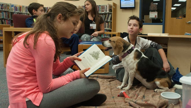 Trista Yandach, left, and Connor Spring read along with a dog Named Samantha at the Deptford Public Library. Pets are a silent partner for children learning to read, according to Furever as Friends, a pet therapy group. kids Ñ many who are afraid of animals or perhaps who aren't allowed to have pets at home practice reading aloud to pets as part of the SMILE Reading program.