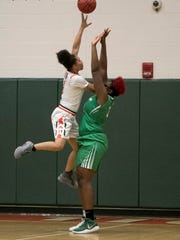 D'Shannon Powell of Dunbar takes a shot over Chaniya Clark of Fort Myers in the girls basketball district championship on Friday, Feb. 9, 2018, in Fort Myers.