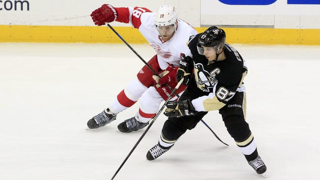 Pittsburgh Penguins center Sidney Crosby, right, handles the puck as Detroit Red Wings center Joakim Andersson (18) pressures Feb. 11, 2015.