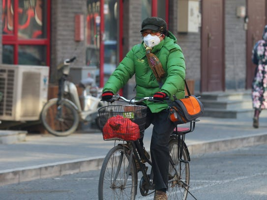 A Chinese woman wears mask while riding on a bicycle