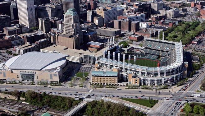FILE - This May 20, 2005, file photo shows Jacobs Field (now Progressive Field), right, and Gund Arena (now Quicken Loans Arena) in Cleveland. The Cavaliers will raise their NBA title banner tonight and the Indians will host the Chicago Cubs in Game 1 of the World Series.