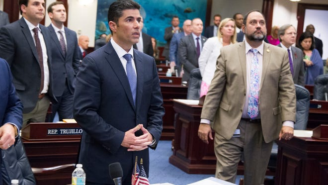 Florida House bill sponsor Rep. Jose Oliva, center, R- Hialeah, watches the vote board at the Capitol in Tallahassee, Fla., on March 7, 2018. The Florida House passed a school safety bill that includes new restrictions on rifle sales and a program to arm some teachers.