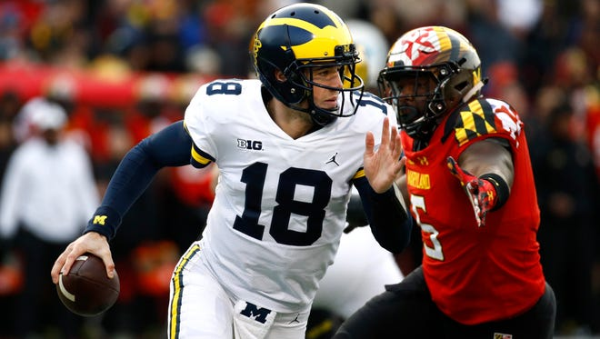 Michigan quarterback Brandon Peters looks for a receiver as he is pressured by Maryland defensive lineman Cavon Walker in the first half of U-M's 35-10 win on Saturday in College Park, Md.