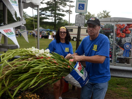 Vineland's Jersey Fresh Festival committee members Sandy and Gary Forosisky, of Vineland, put out Jersey Fresh glads for sale during the festival, Sunday, Aug. 9, 2015 at Giampietro Park in Vineland.