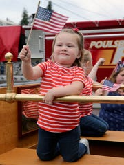 Charlie Richter, 2, of Poulsbo practices her flag waving on the back of an antique fire truck before the start of the Fourth of July Parade in Keyport on Wednesday.