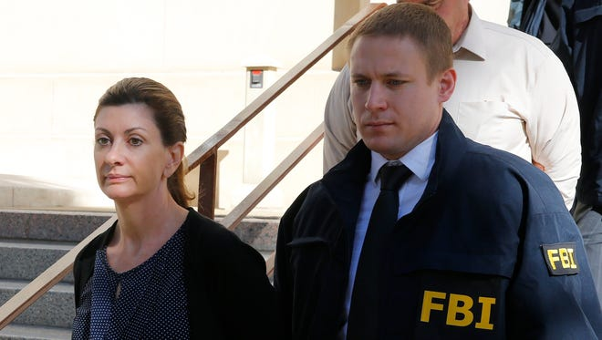 Nancy Love, current assistant principal at Maxine Silva Health Magnet High School and former assistant principal at Austin High School, is led to the El Paso County Jail early Wednesday morning after surrendering to the FBI in connection with the El Paso Independent School District cheating scandal.