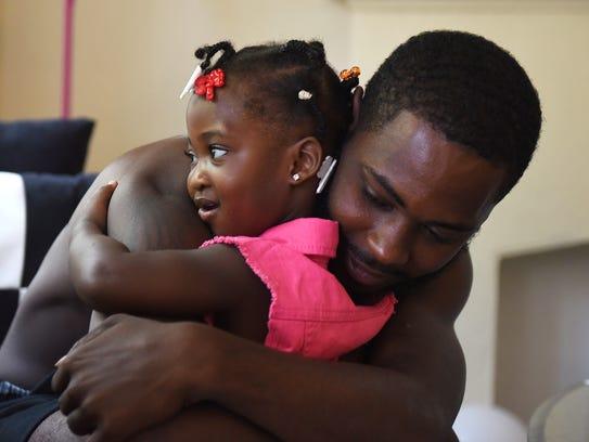 Kalaya Hull-Mason, 2, hugs her father, Laron Mason.