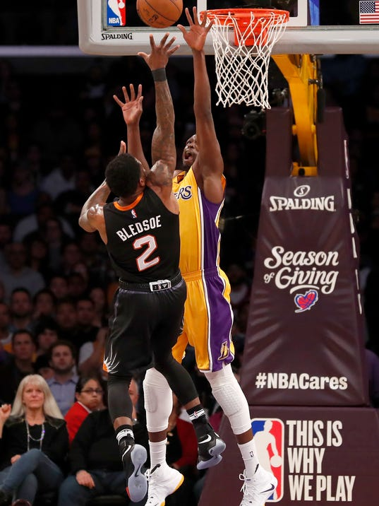 Phoenix Suns guard Eric Bledsoe, left, shoots over Los Angeles Lakers forward Luol Deng during the first half of an NBA basketball game, Friday, Dec. 9, 2016, in Los Angeles. (AP Photo/Ryan Kang)