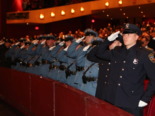 New police officers salute the flag as the Westchester
