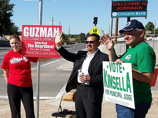 "William ""Bill"" Kinsella, right, candidate for Las Cruces municipal judge; Eli Guzman, candidate for City Council District 1; and April Christensen, a supporter of Guzman's, hold signs near Jornada Elementary School on Tuesday afternoon."