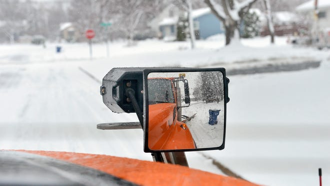 Mirrors on the front corner of a snowplow driving in St. Cloud in December 2015 offer a good view back down the side of the truck.