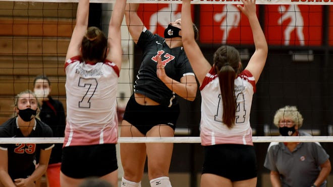 Bedford's Kamryn Wolf (center) goes up to spike as Monroe blockers Emma Chappell (7) and Kamryn Bice (14) block for Monroe Thursday night.