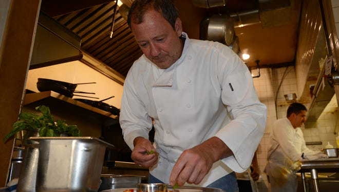 Kevin Kohler, owner and chef at Cafe Panache, in the kitchen of his restaurant prepares a tomato dish.
