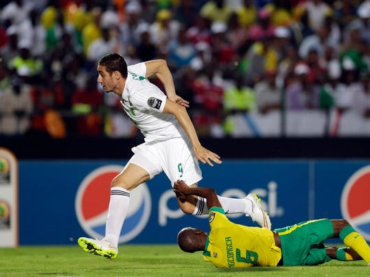 Algeria's Ishak Belfodil, left, is challenged by South Africa's Anele Ngcongca, during the African Cup of Nations Group C soccer match between Algeria and South Africa in Mongomo, Equatorial Guinea, Monday, Jan. 19, 2015. (AP Photo/Themba Hadebe)