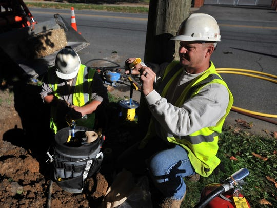 Lancaster Municipal Gas employee Rick Hanna, right, pulls a blade of grass off a pipe he and Jared Roley will use to connect a service line to the main natural gas on Fair Avenue.