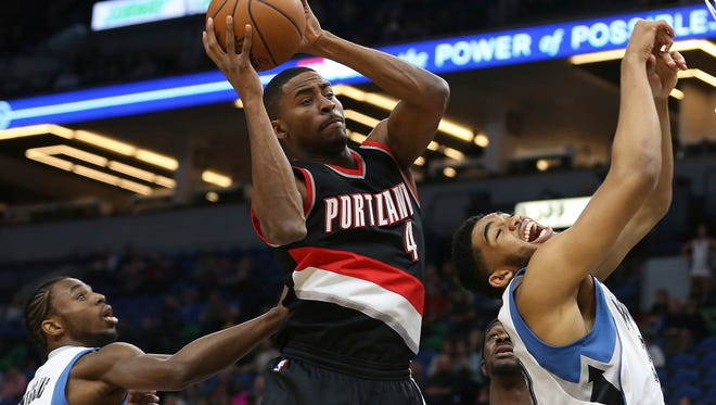 Portland Trail Blazers forward Maurice Harkless (4) grabs a rebound ball away from Minnesota Timberwolves center Karl-Anthony Towns, right, in the first half of an NBA basketball game, Monday, April 3, 2017, in Minneapolis. (AP Photo/Stacy Bengs)