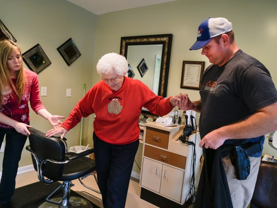 Donald Smith helps his grandmother, Reba Hahn, who he cares for, out of a barber chair at the Cutting Room after her haircut in Verona on Wednesday morning.