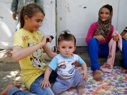 Children go about their lives at the Oncupinar camp for Syrian refugees next to the border crossing with Syria, near the town of Kilis in southeastern Turkey, in June.