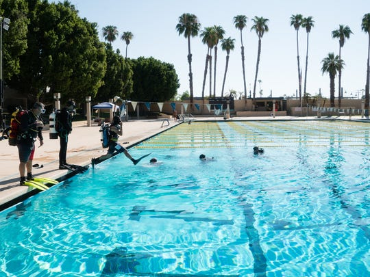 Local divers jump into the Palm Springs Pool to begin