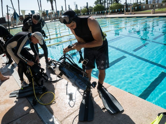 Divers get ready to jump into the pool for training
