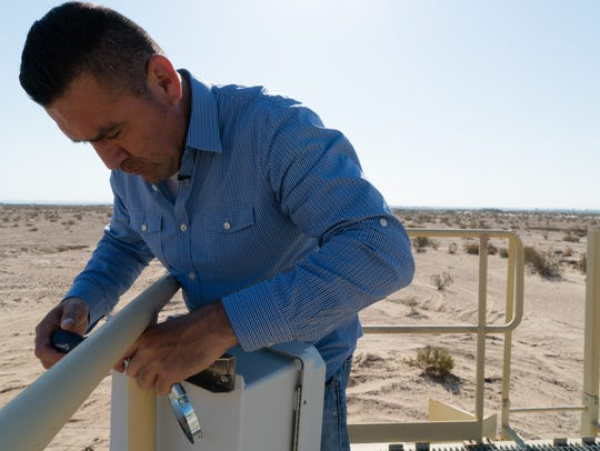 Humberto Lugo, of Comité Civico, installs an air monitor