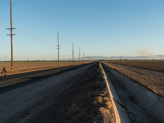 A man rides his bicycle on a road stretching north from the Mexican border in Calexico, Calif. Air pollution in the Imperial Valley comes from a variety of sources including agricultural activities, the disturbance of desert land, vehicle exhaust, and industrial pollution from Mexicali, Sept. 6, 2016.