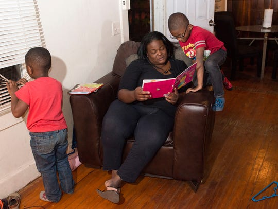 Shenevia Jones, center, reads to her 6-year-old, Trystian,