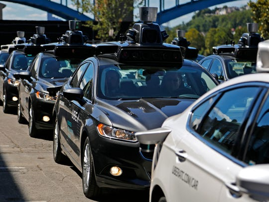 A group of self-driving Uber vehicles position themselves to take journalists on rides during a media preview at Uber's Advanced Technologies Center in Pittsburgh. U.S. President Donald Trump's economic plans are nothing if not ambitious, including his vision of creating 25 million jobs over 10 years. However, the widespread use of robots and automation by companies has increasingly allowed businesses to operate with fewer workers. For example, Uber is experimenting with self-driving cars, and restaurant chains like Eatsa can now serve lunch and dinner through an automated order-and-payment system, and no cashiers or servers are necessary. (AP Photo/Gene J. Puskar, File)