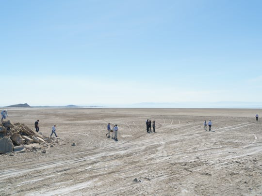 Local and state officials walk out onto the exposed lakebed of Red Hill Bay during a Salton Sea tour on March 16, 2017.