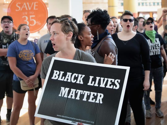 Demonstrators march through the West County Mall protesting