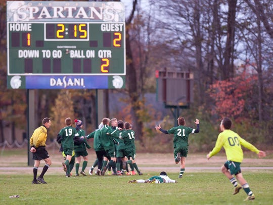 The Peoples Academy boys soccer team celebrates its game-winning goal in overtime against Winooski in the Division III semifinals on Tuesday afternoon in Winooski.