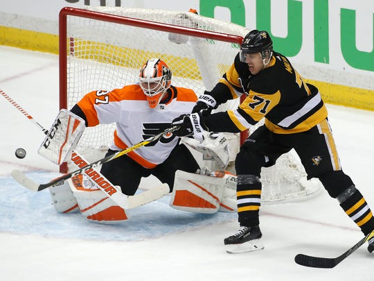 Pittsburgh Penguins' Evgeni Malkin (71) cannot get his stick on a puck in front of Philadelphia Flyers goaltender Brian Elliott (37) during the first period in Game 2 of an NHL first-round hockey playoff series in Pittsburgh, Friday, April 13, 2018. (AP Photo/Gene J. Puskar)