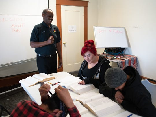 Ndolo teaches the class, as student Talena Shirley, right, studies the GED guide.