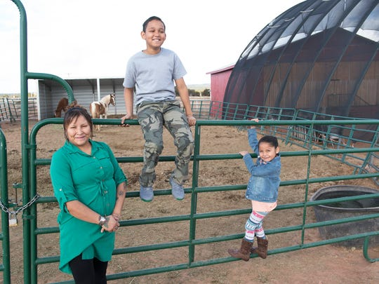 Lisa Lee, her son Zachary and daughter Kadence look at the horses outside the God's Living Water Church in St. Michaels, on the Navajo Nation in Arizona.