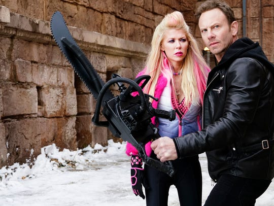April (Tara Reid) and Fin (Ian Ziering) brandish a chainsaw in 'Sharknado 5: Global Swarming.'