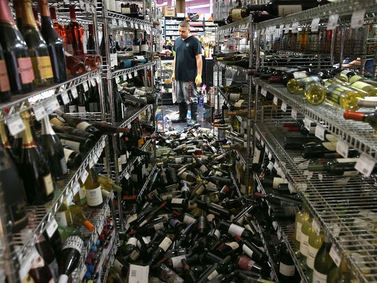 A worker looks at a pile of wine bottles that were