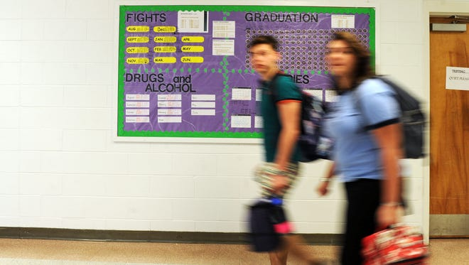 Students walk past a board with data listing the number of fights, drug and alcohol violations and tardiness Monday morning at Owen High School.