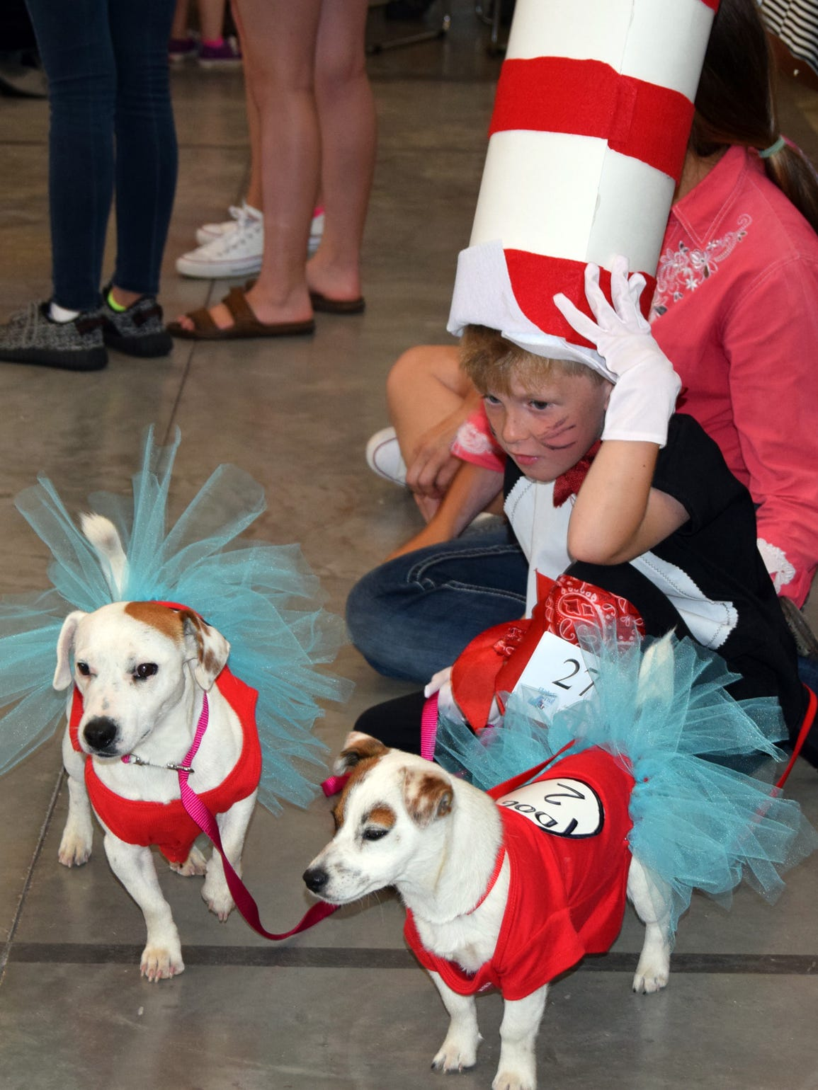 A young girl dress as The Cat in the Hat and her dogs