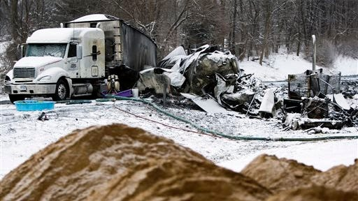 The charred remains of vehicles and debris sit on I-94, Saturday, Jan. 10, 0215, as road crews work to clear them the day after a series of crashes closed the highway between mile markers 88 and 92 in eastern Kalamazoo County, near Galesburg, Mich.